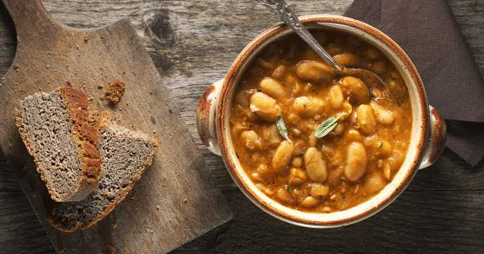 white bean stew in a large dish with bread, rustic