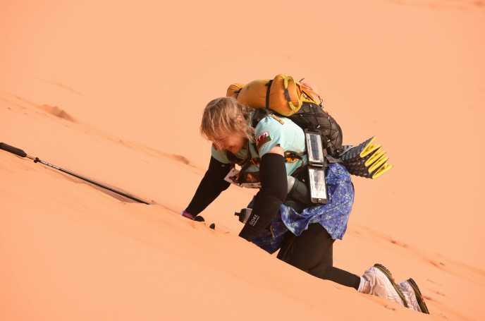 An exhausted Elaine struggles to the top of a very high, very steep, sand dune
