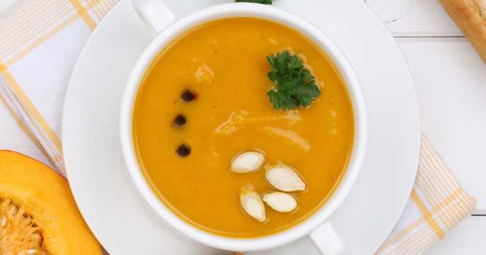 Pumpkin soup with fresh pumpkins in bowl