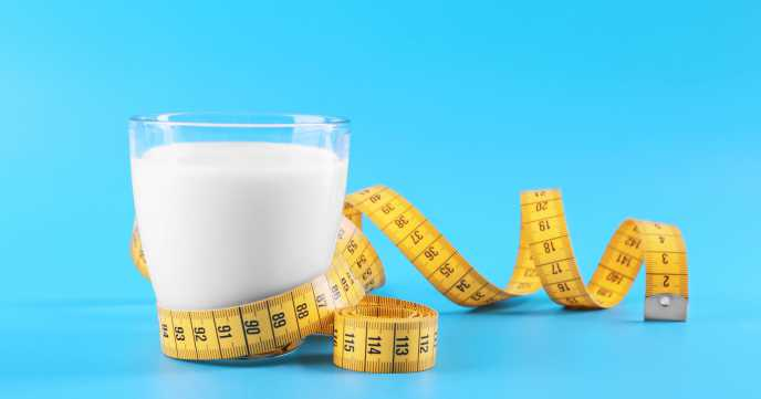 glass of calcium rich milk with tape measure