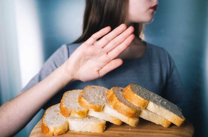 woman pushing bread away with hand