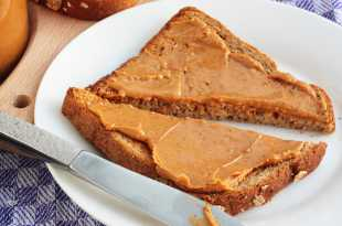 Slice of toasted wholemeal bread spread with smooth nut butter