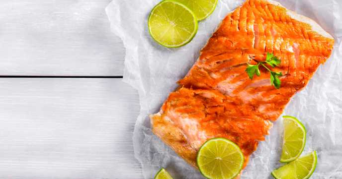 cooked salmon with slices of lime scattered around