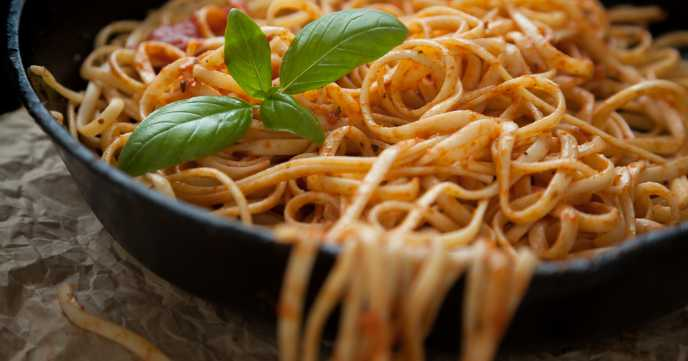 Linguine with red sauce and a sprig of basil