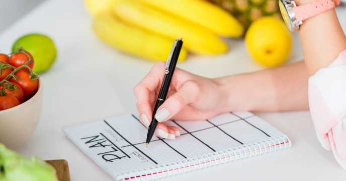 woman making her own diet plan in notebook